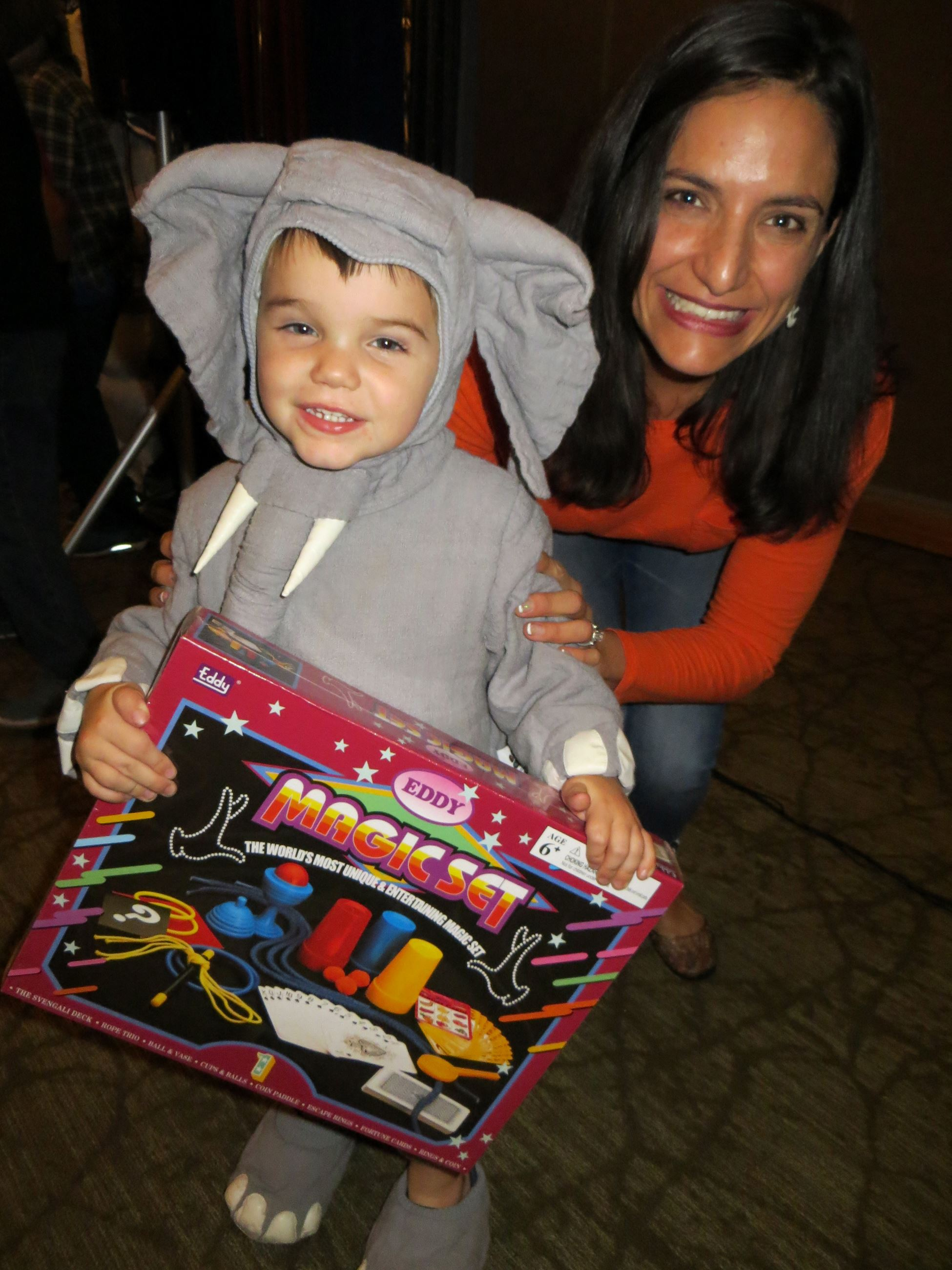 Boy in elephant costume holding up prize with Mom