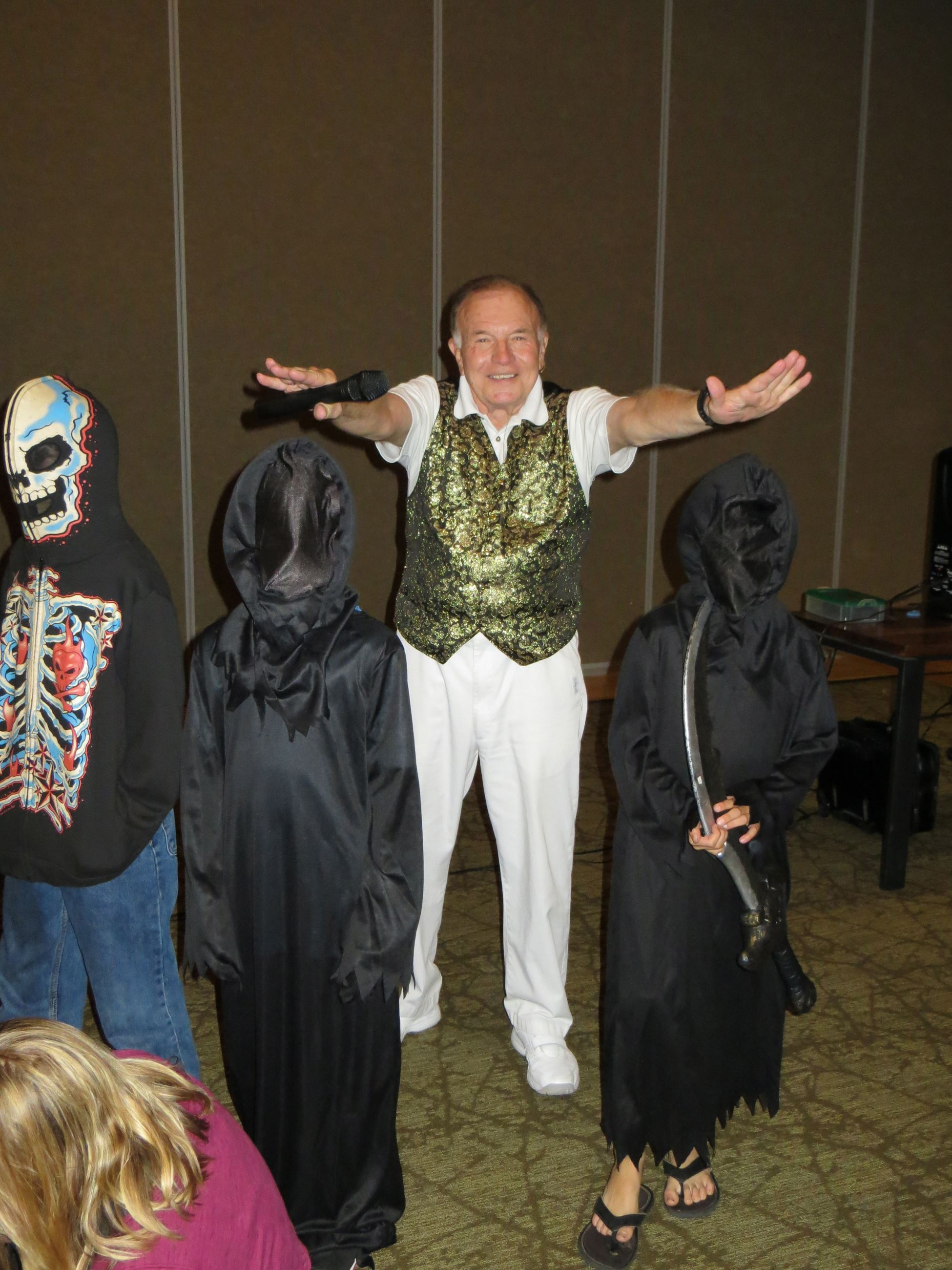 Magician with hands over two kids in phantom costumes