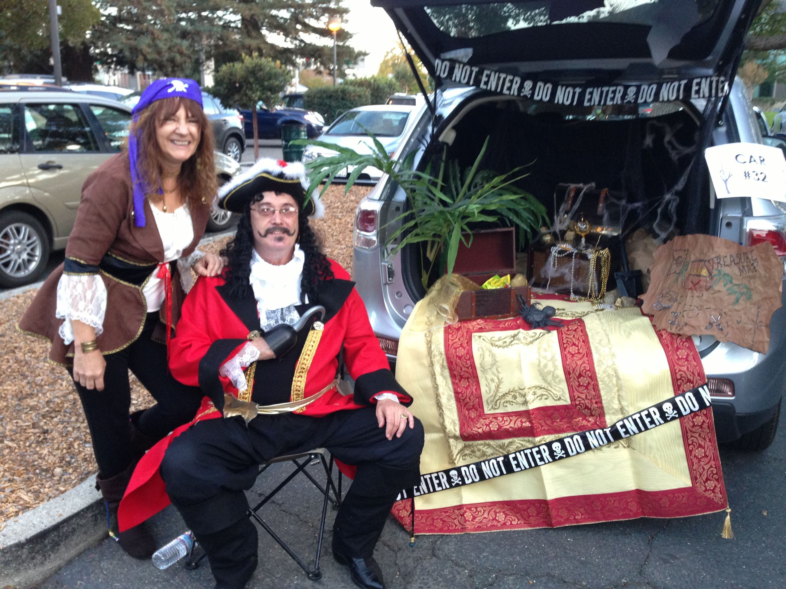 Adults in pirate costumes next to priate theme car trunk