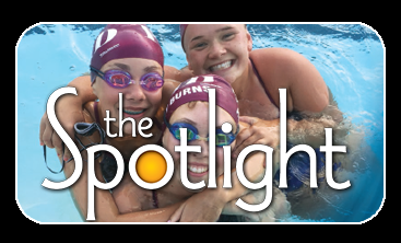 Three teen girl swimmers in group hug in pool