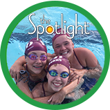 Three girl swimmers in group hug in pool