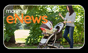 Young mom pushing stroller in park looking at cell phone