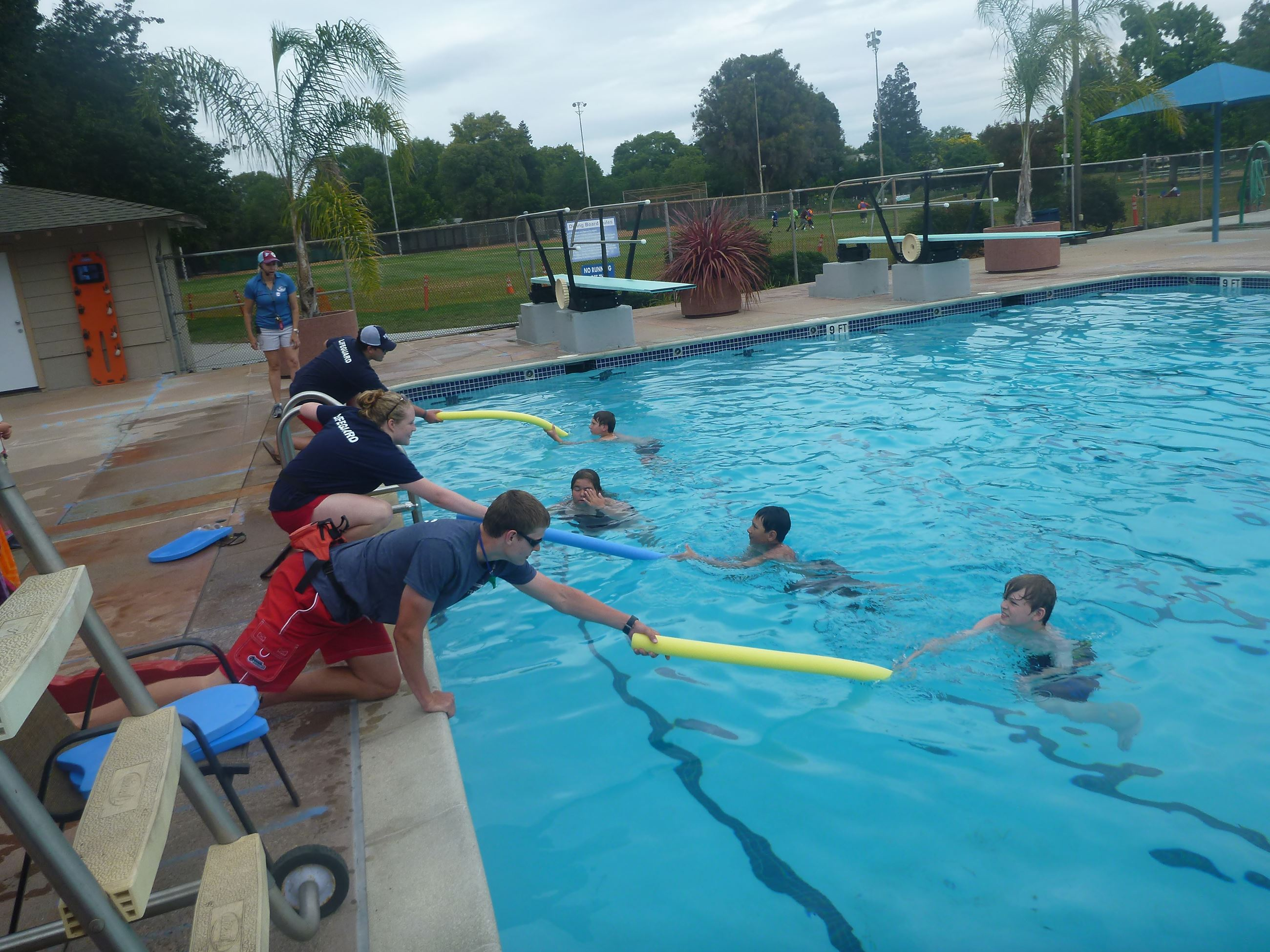 Lifeguards demonstrating reaching assists at Pool Safety Day