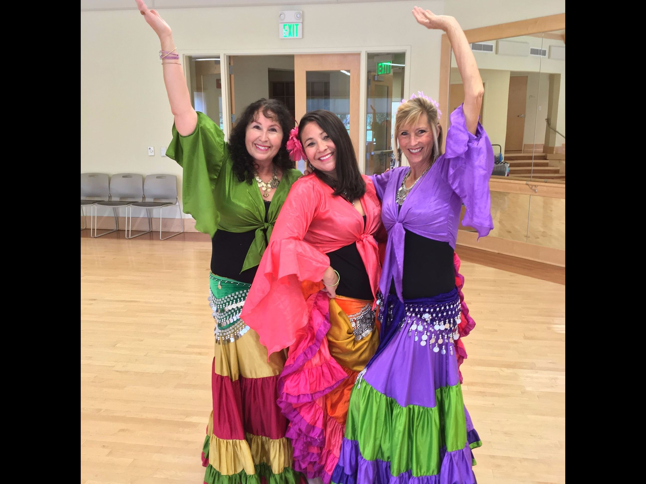 Three adult female belly dancers striking pose