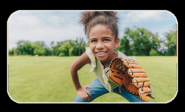 Girl with softball mitt crouched down and ready to catch ball