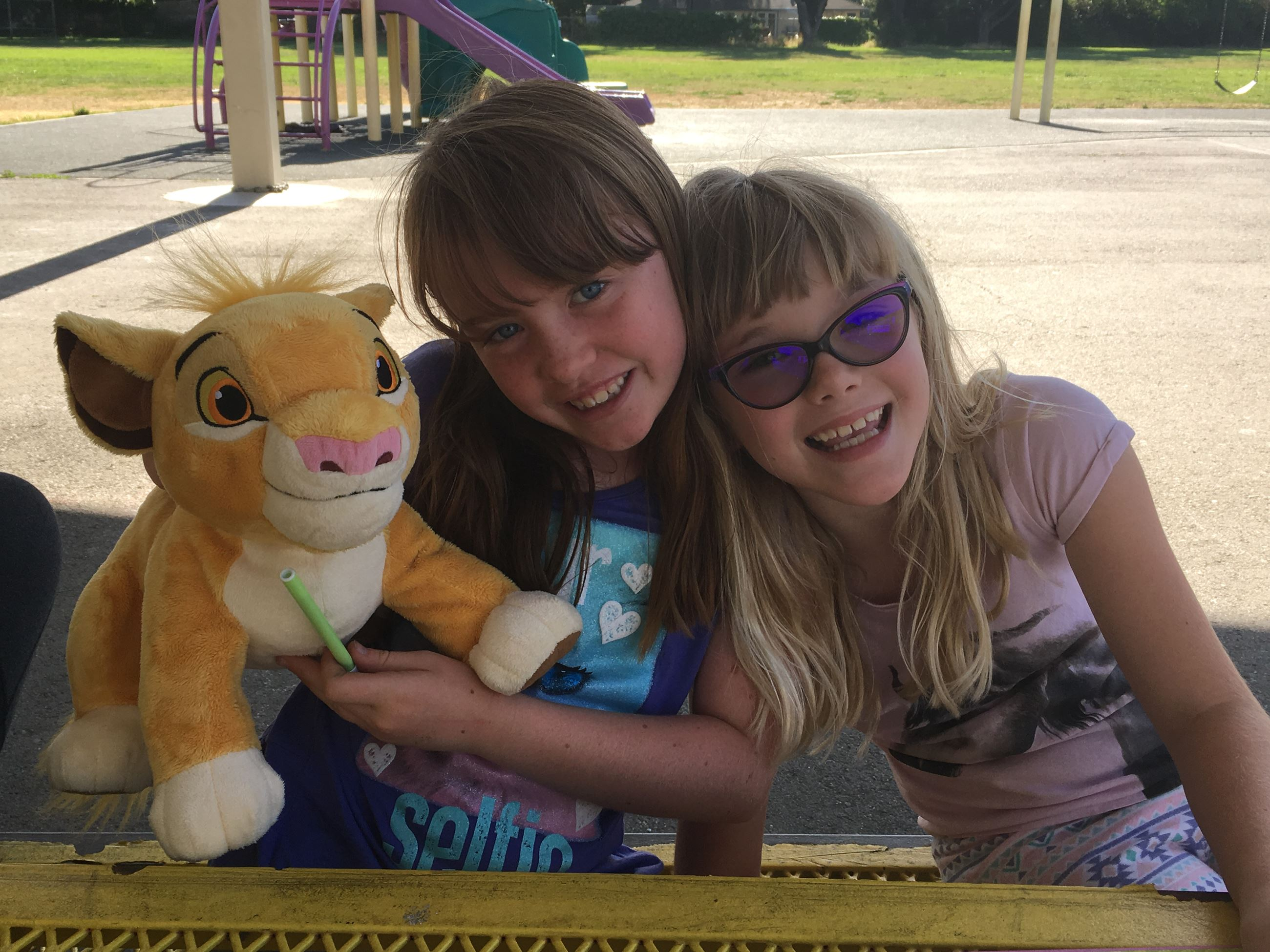 Two smiling girls with Simba Stuffed animal