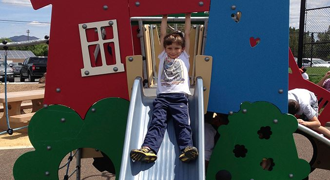 Young boy sliding down slide