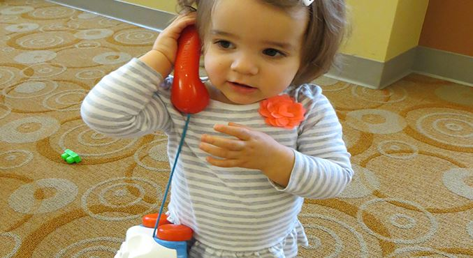 Toddler girl on old fashion plastic phone