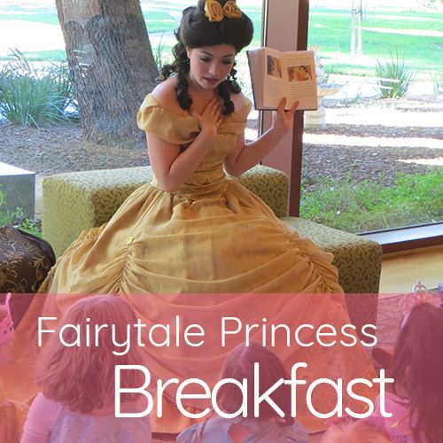 Princess Belle in fancy yellow dress reading to group of young girls