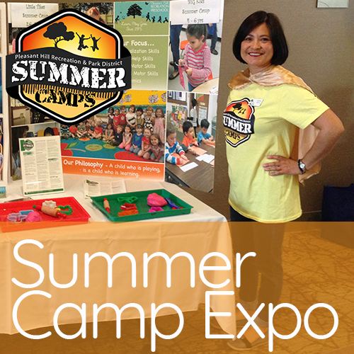 Lady in yellow summer camp T-shirt and camp in front of table top display