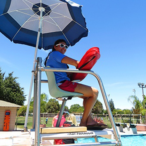 A female lifeguard sitting on a tour by the pool